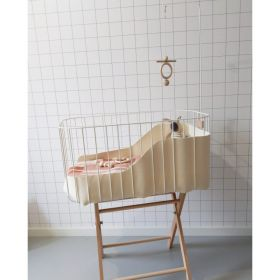 Tall white baby crib with wooden legs, wooden cot mobile and mattress with bunny toy and teething rings inside it.