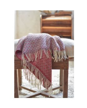 red and grey wool blanket with flower pattern displayed on a chair with pillow