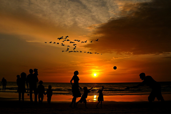 Family playing on the beach whilst the sun is setting