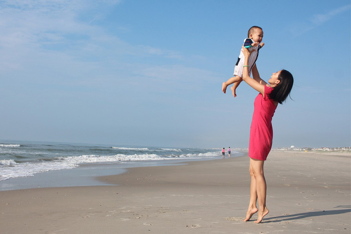 Mum lifting her baby up in the air on the beach and both laughing