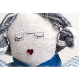 Handmade woolen old granny hand puppet with grey platted hair, glasses and blue scarf close up