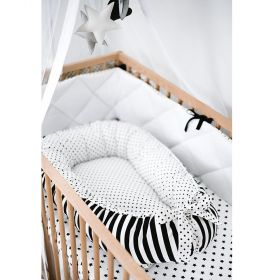 white baby nest with back dots on the inside and on the ribbon at the end and black and white stripes  on the outside in a wooden cot