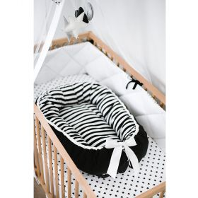 baby nest with stripes in the inside and black on the outside with white ribbon at the end  in a wooden cot