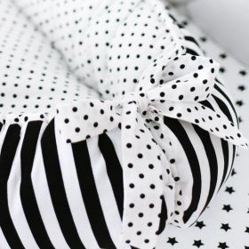 white baby nest with black dots on the inside and on the ribbon at the end and black and white stripes  on the outside