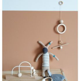 simple wooden cot mobile having on the wall, next to bunny toy a