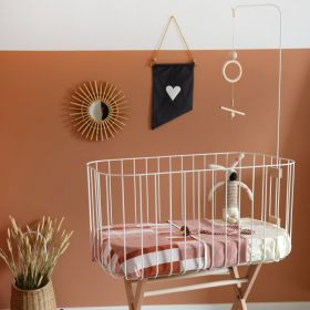 Tall white baby crib with wooden legs, wooden cot mobile and mattress with bunny toy inside.