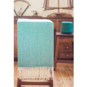 Turquoise and white 100% sheep wool blanket with thorn pattern on a chair