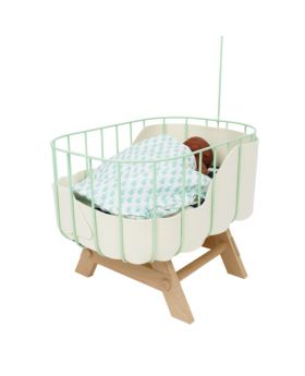 small doll baby crib made with mint green aluminium side, with white felt around inside and natural wood legs with a baby doll and blanket inside it