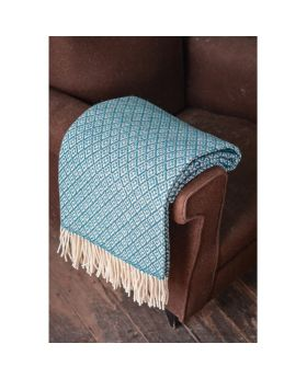blue wool blanket with flower pattern folded on the side of a brown sofa