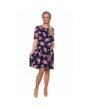 Pregnant woman with long blond hair wearing elegant maternity chiffon dress with flower pattern with high heels.