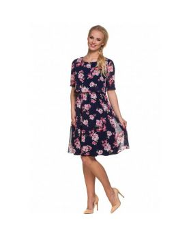 Pregnant woman with long blond hair wearing elegant maternity chiffon dark blue dress with pink flower pattern with high heels.