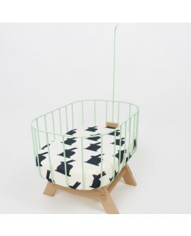 small doll baby crib made with mint green aluminium side, with white felt around inside and natural wood legs with a black and white mattress inside it